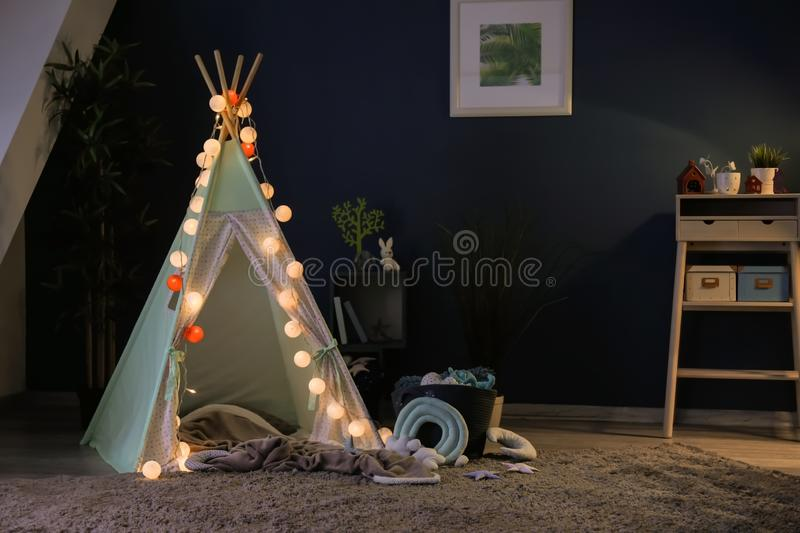 Cozy play tent for kids with glowing garland in room interior royalty free stock photo