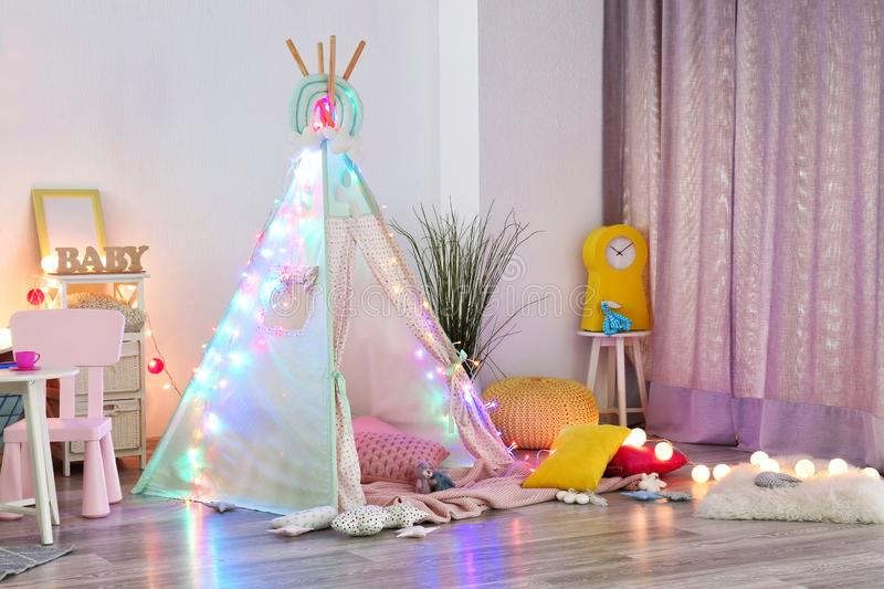 Cozy play tent for kids with glowing garland in room interior royalty free stock photos