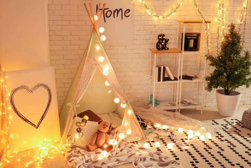 Cozy play tent for kids with glowing garland in room interior stock photography