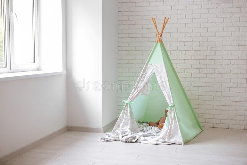 Cozy play tent for kids near white brick wall indoors royalty free stock image