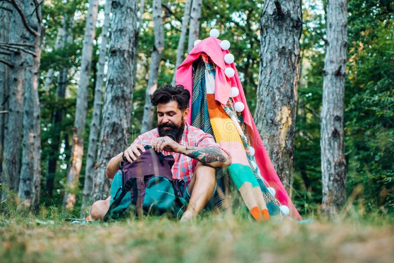 Cozy play tent for man in forest park. Hiking and outdoor recreation concept with flat camping travel. Handsome bearded royalty free stock image