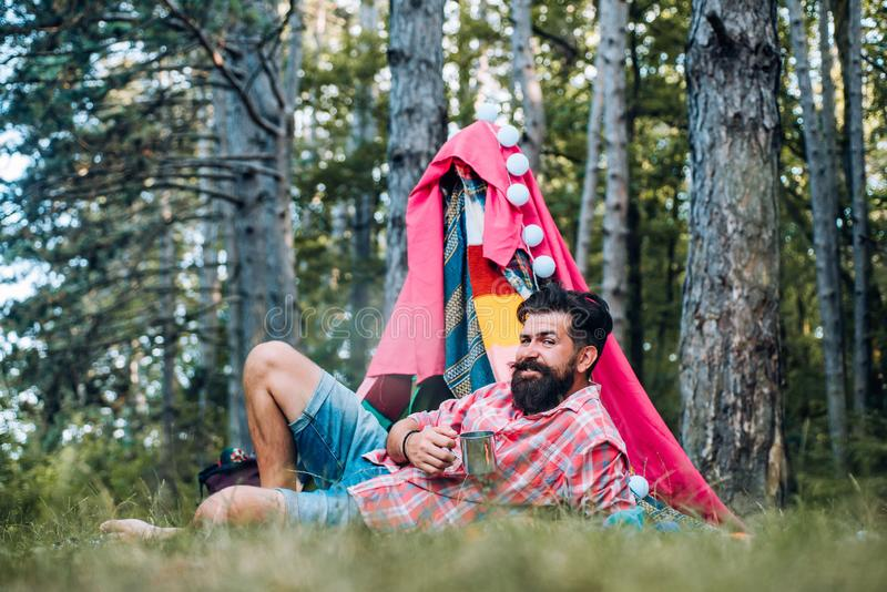 Cozy play tent for man on nature over sky background - isolated. Handsome bearded man having fun in adventure Park. stock photo