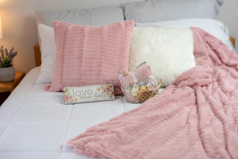 Cozy guest bed in white, gray and pink. Cozy and relaxing bed in white, gray and pink palette stock image