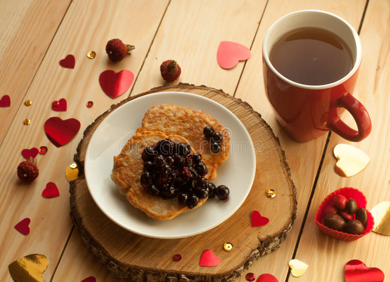 A cozy rustic composition with a red tea cup, a plate of pancakes with jam, and decorative hearts on a wooden surface royalty free stock photography