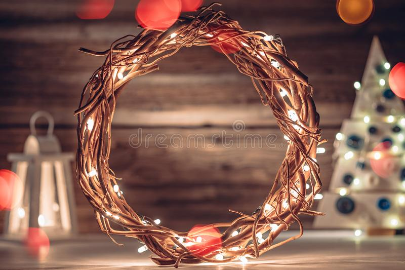 Cozy rustic composition with wreath, Christmas tree and lantern on old wooden boards background royalty free stock image