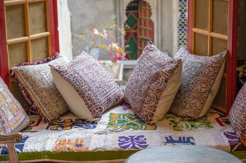 A cozy seating area near the window with colorful pillows with a wonderful view of the courtyard in Udaipur, Rajasthan, India stock image