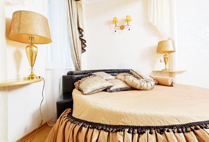 Cozy soft beautiful round bed in classical golden bedroom. Close up stock photos