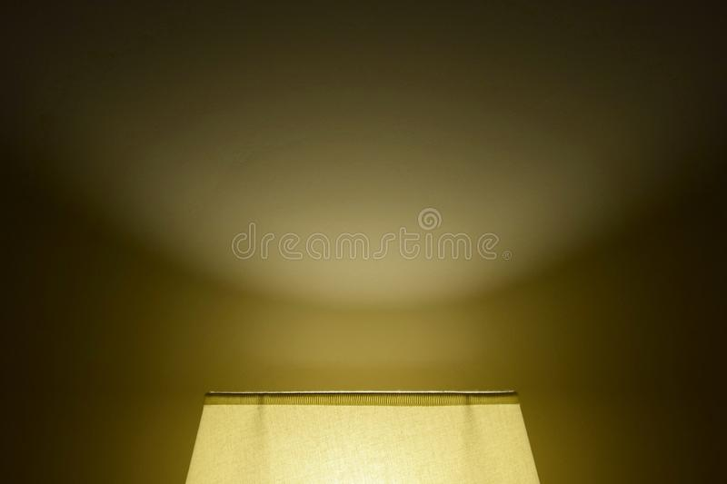 A cozy soft light from a lamp shade on the wall in a dark room. Backlight from below stock images