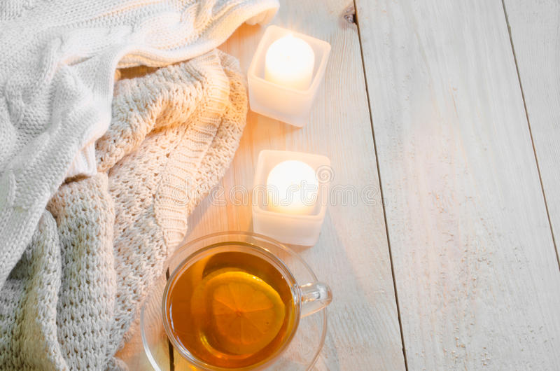 Cozy and soft winter background. Warm sweaters or blankets, candles, cup of tea. royalty free stock image