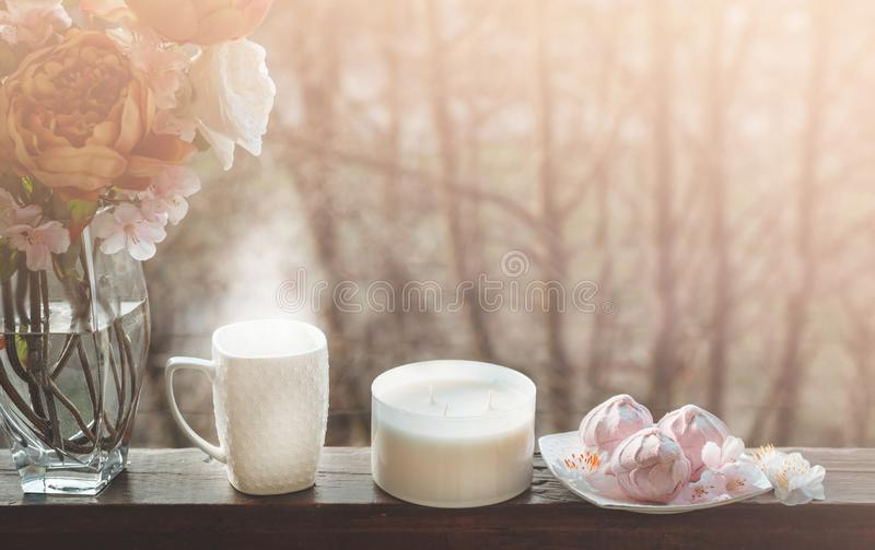 Cozy spring still life: cup of hot tea with spring bouquet of flowers on vintage windowsill with a pink marshmallow. Spring. Apartment stock photo