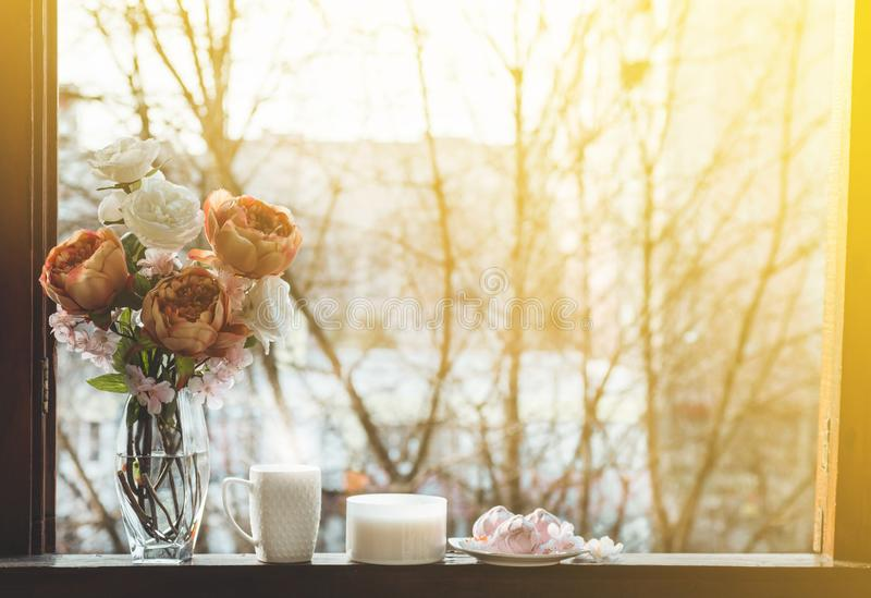 Cozy spring still life: cup of hot tea with spring bouquet of flowers on vintage windowsill with a pink marshmallow. Spring. Apartment stock image