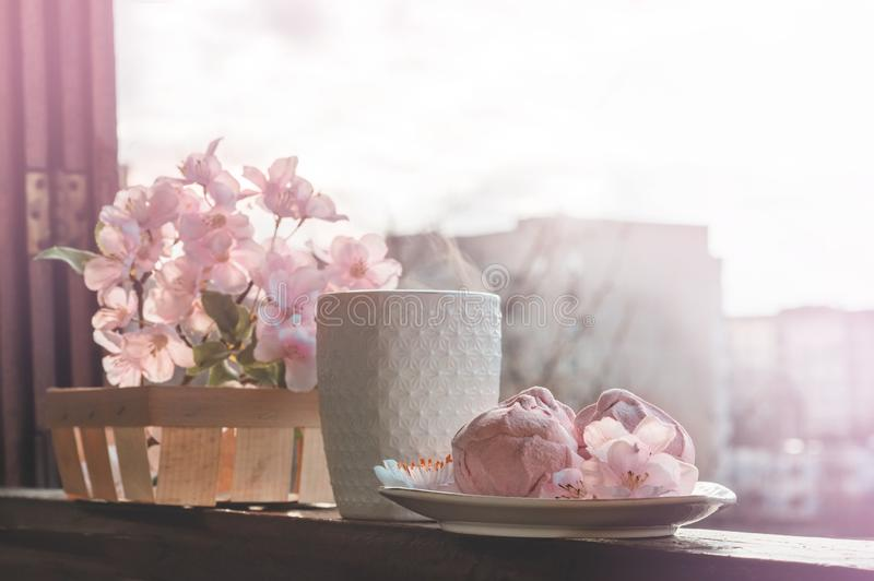 Cozy spring still life: cup of hot tea with spring bouquet of flowers on vintage windowsill with a pink marshmallow. Spring. Apartment royalty free stock photography