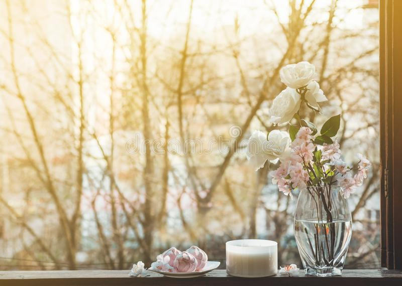 Cozy spring still life: cup of hot tea with spring bouquet of flowers on vintage windowsill with a pink marshmallow. Spring. Apartment royalty free stock images