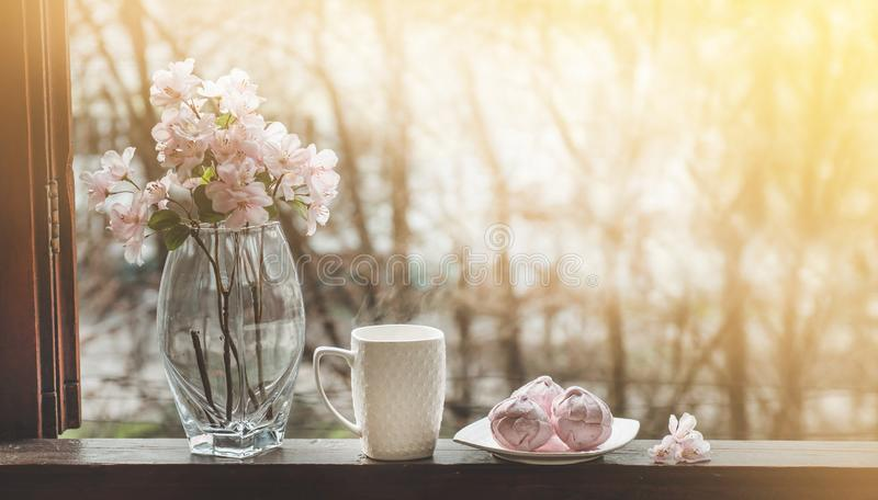 Cozy spring still life: cup of hot tea with spring bouquet of flowers on vintage windowsill with a pink marshmallow. Spring. Apartment royalty free stock image