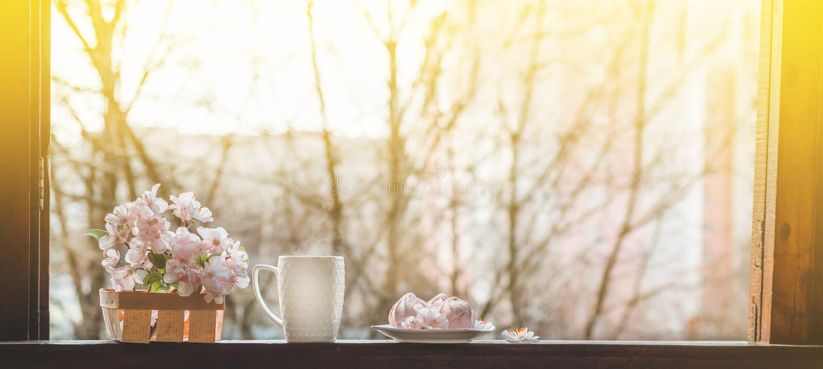 Cozy spring still life: cup of hot tea with spring bouquet of flowers on vintage windowsill with a pink marshmallow. Spring. Apartment royalty free stock photo