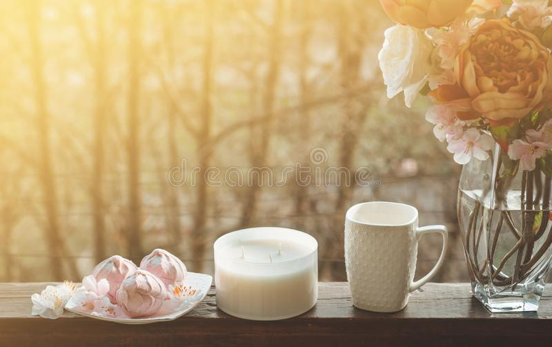 Cozy spring still life: cup of hot tea with spring bouquet of flowers on vintage windowsill with a pink marshmallow. Spring. Apartment stock images