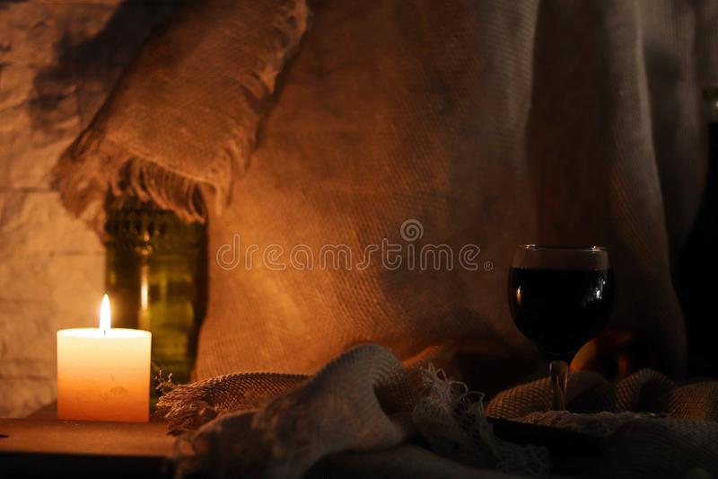 A glass of red wine standing on table with reflection of candle light and bottle of olive oil on sackcloth background stock images