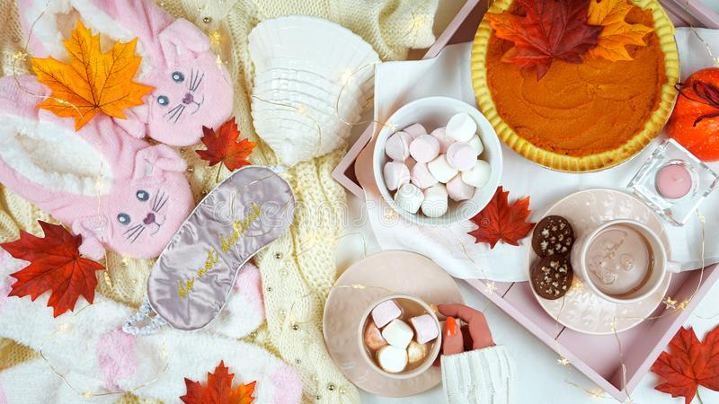 Cozy Thanksgiving flatlay overhead with pumpkin pie and hot chocolate. Cozy autumn Thanksgiving in bed flatlay overhead with cosy sweater, slippers, socks and royalty free stock photography
