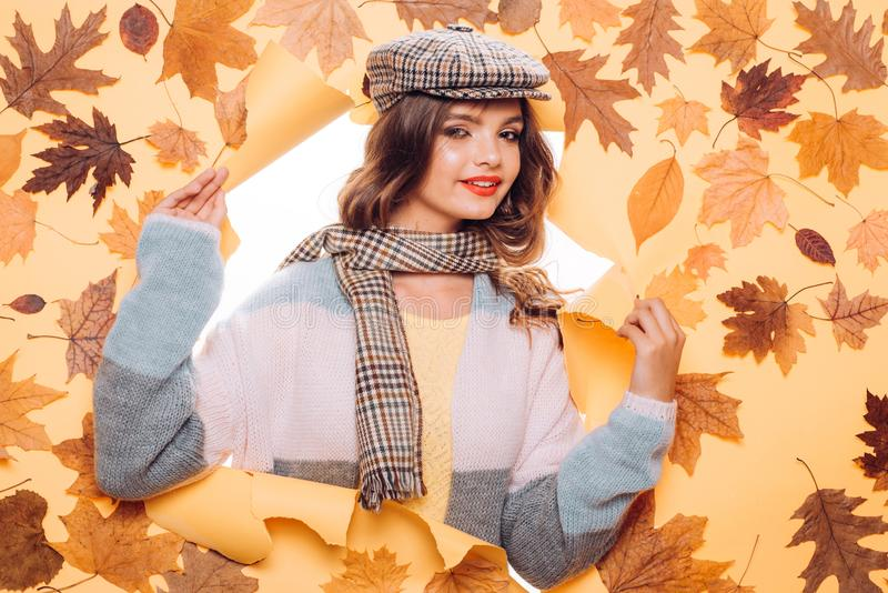 Cozy up to herself. Fashion girl look through torn paper with autumn leaves. Fall look of vogue model. Casual fashion stock image