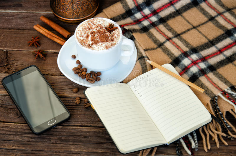 Cozy vacation. Latte mug, notebook, pencil, phone, plaid and coffee beans. View from above stock photography