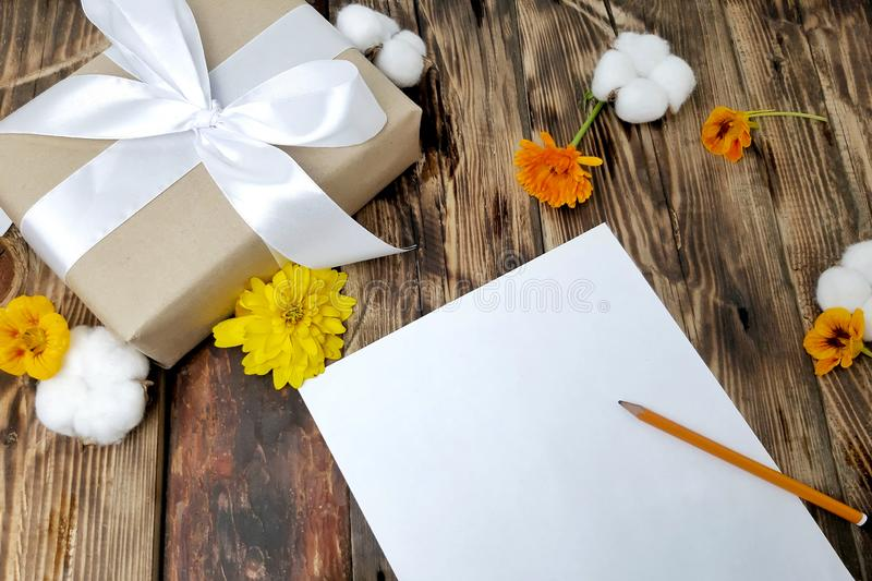 Cozy warm autumn mock up background. Gift box, empty card, flowers on wooden desk. Selective focus. Hygge lifestyle fall holiday design royalty free stock photos