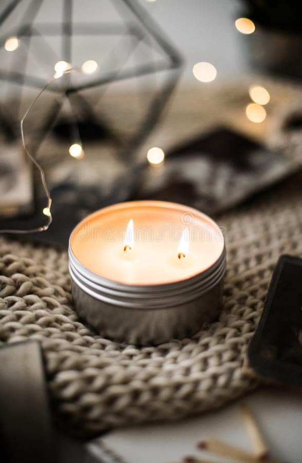 Cozy warm home decoration with burning candle and bokeh lights. On background, calm and relax room interior closeup royalty free stock image