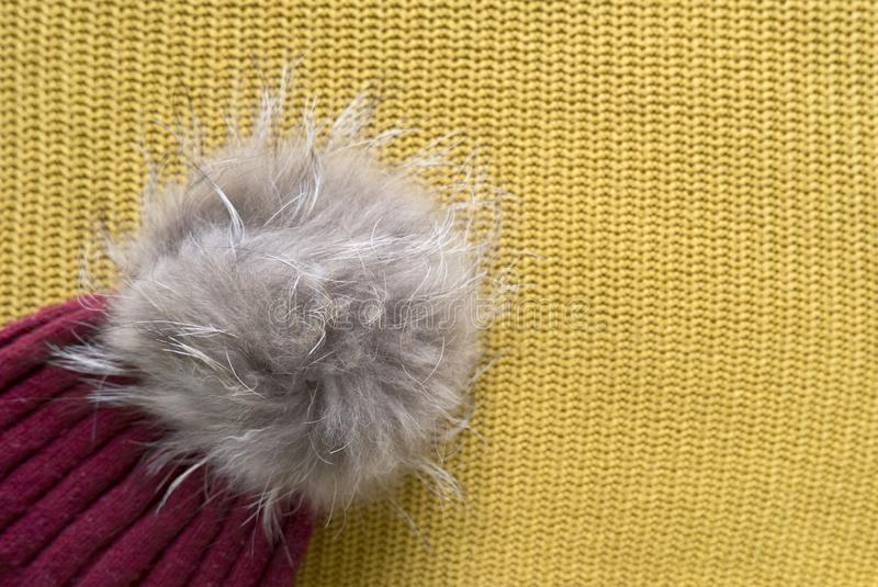 Cozy and warm winter flat lay with copy space. Close up of dark red knitted hat with fur pompom on yellow woolen background. Cozy and warm winter flat lay with royalty free stock images