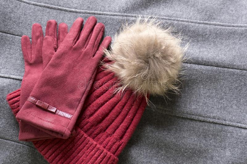 Cozy and warm winter flat lay with copy space. Dark red knitted hat with fur pompom and burgundy gloves on gray background. Cozy and warm winter flat lay with royalty free stock photo
