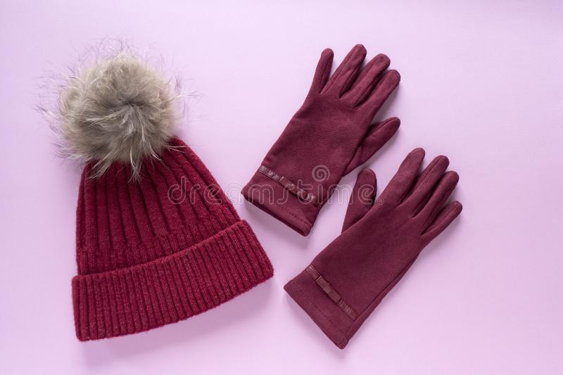 Cozy and warm winter flat lay with copy space. Dark red knitted hat with fur pompom and burgundy gloves on pink background. Cozy and warm winter flat lay with stock image