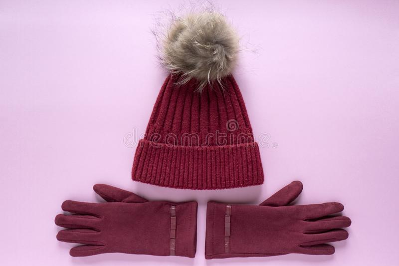 Cozy and warm winter flat lay with copy space. Dark red knitted hat with fur pompom and burgundy gloves on pink background. Cozy and warm winter flat lay with stock photography