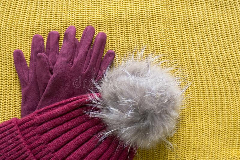 Cozy and warm winter flat lay with copy space. Dark red knitted hat with fur pompom and burgundy gloves on yellow background. Cozy and warm winter flat lay with stock photo