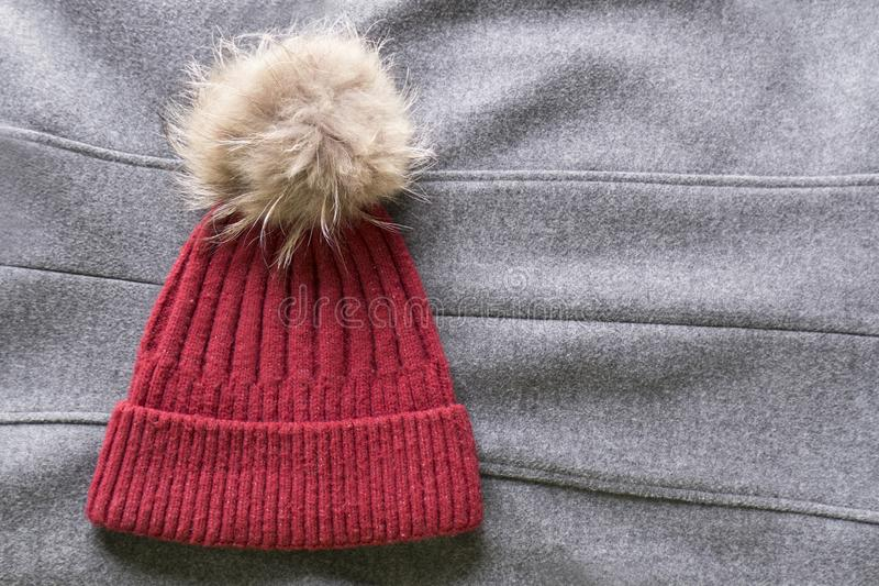 Cozy and warm winter flat lay with copy space. Dark red knitted hat with fur pompom on gray woolen crumpled background. Cozy and warm winter flat lay with copy royalty free stock photos