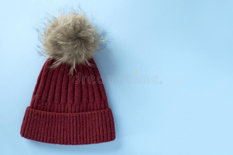 Cozy and warm winter flat lay with copy space. Dark red knitted hat with fur pompom on light blue background. Cozy and warm winter flat lay with copy space. Dark stock photo