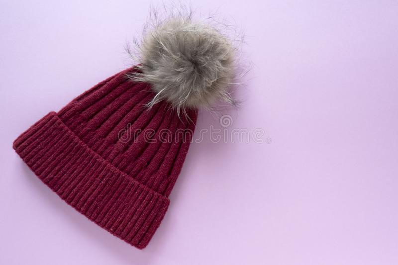 Cozy and warm winter flat lay with copy space. Dark red knitted hat with fur pompom on pink background. Cozy and warm winter flat lay with copy space. Dark red royalty free stock images