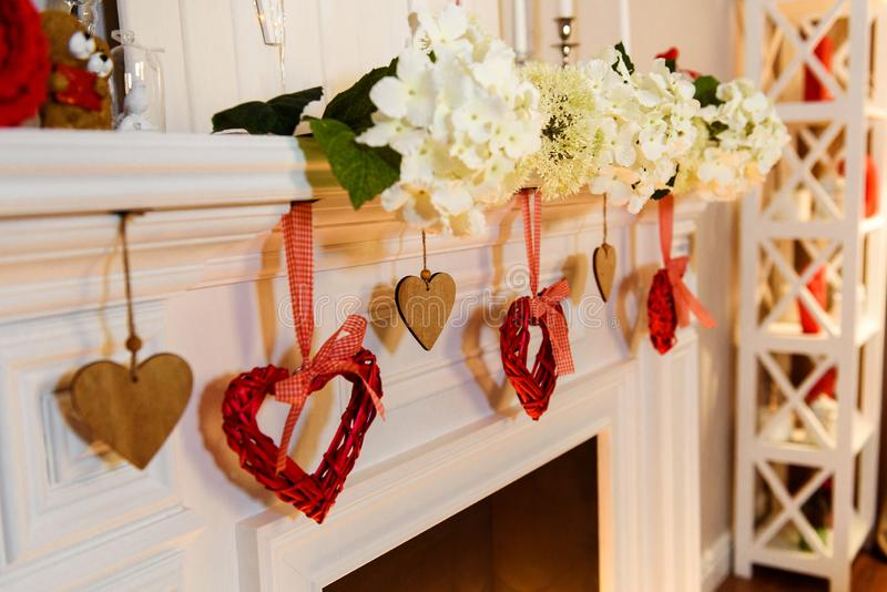 Cozy white fireplace with hanging red hearts on it stock photos