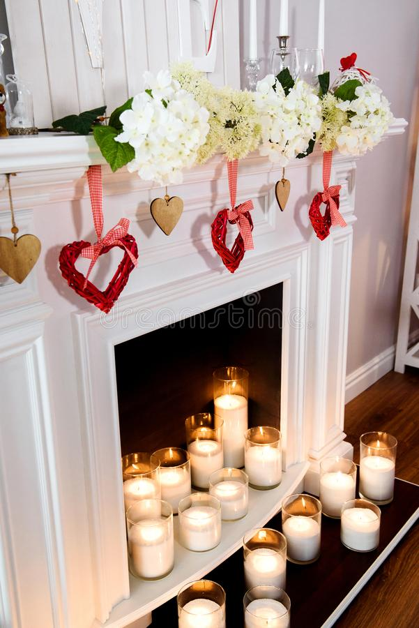 Cozy white fireplace with lots of candles in glass stock photo