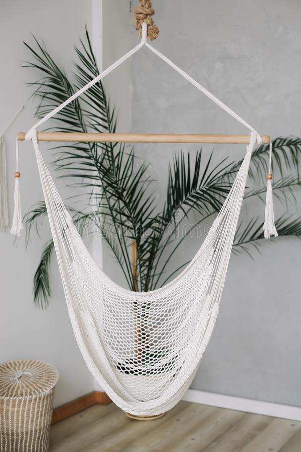 Cozy white hammock in living area, relaxing corner with palm tree at home. Minimal home interior design. royalty free stock photography