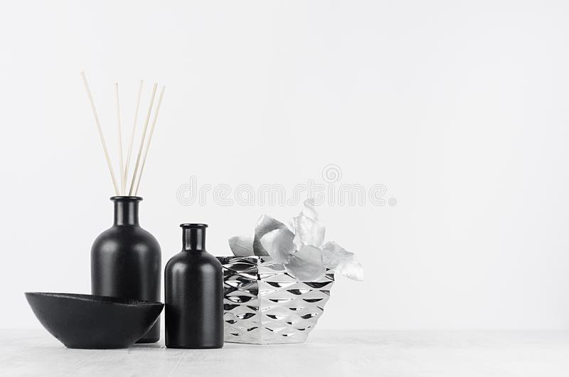 Cozy white home decor with elegant glass bottles, silver vase and decorative metallic branch on wood board with copy space. Cozy white home decor with elegant stock photos