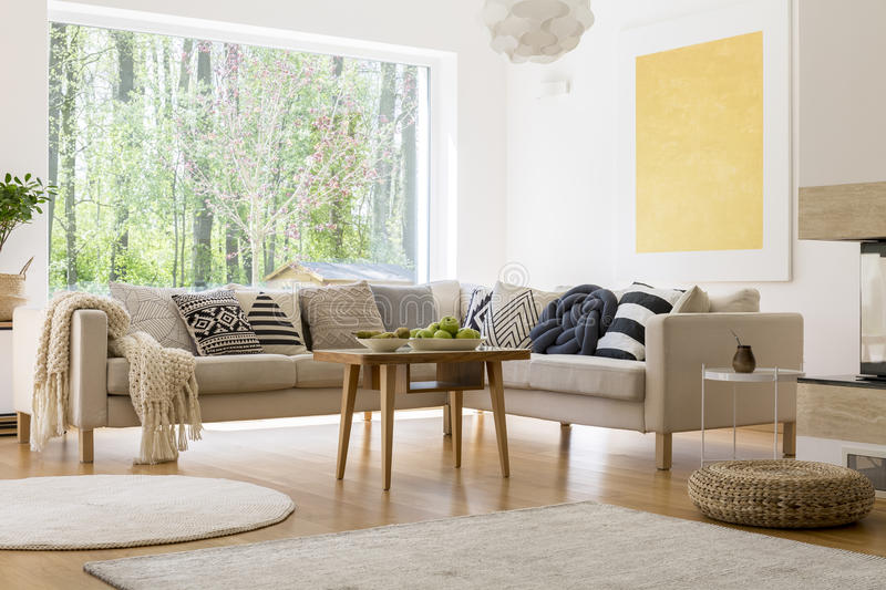 Cozy white room. Cozy white living room with comfortable sofa and wooden coffee table stock photos