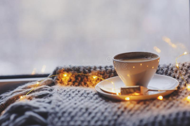 Cozy winter or autumn morning at home. Hot coffee with gold metallic spoon, warm blanket, garland and candle lights. Swedish hygge concept stock image