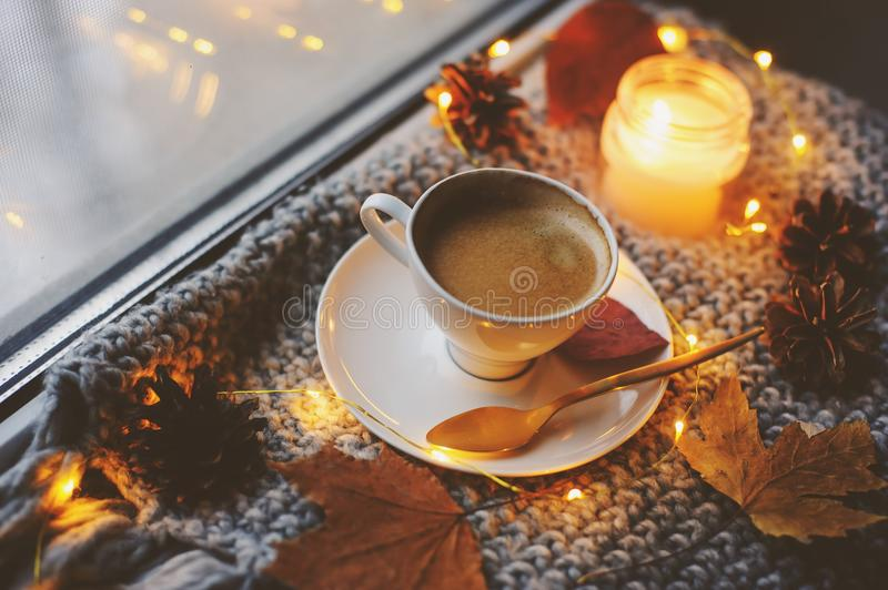 Cozy winter or autumn morning at home. Hot coffee with gold metallic spoon, warm blanket, garland and candle lights. Swedish hygge concept stock photos