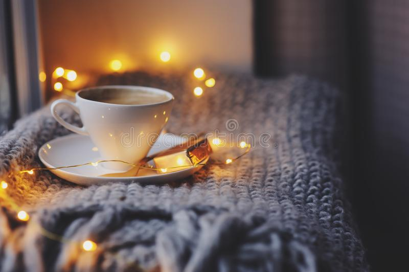 Cozy winter or autumn morning at home. Hot coffee with gold metallic spoon, warm blanket, garland and candle lights. Swedish hygge concept royalty free stock photography