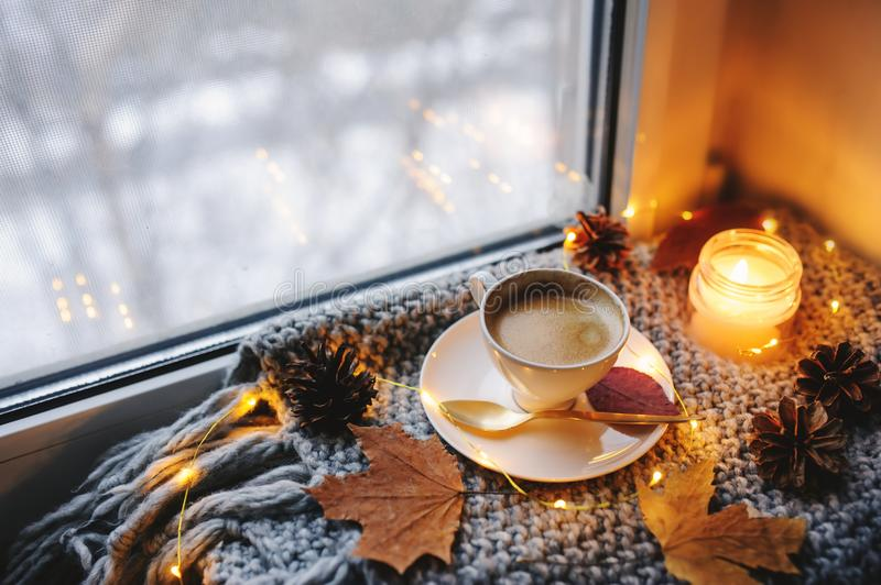 Cozy winter or autumn morning at home. Hot coffee with gold metallic spoon, warm blanket, garland and candle lights. Swedish hygge concept royalty free stock image