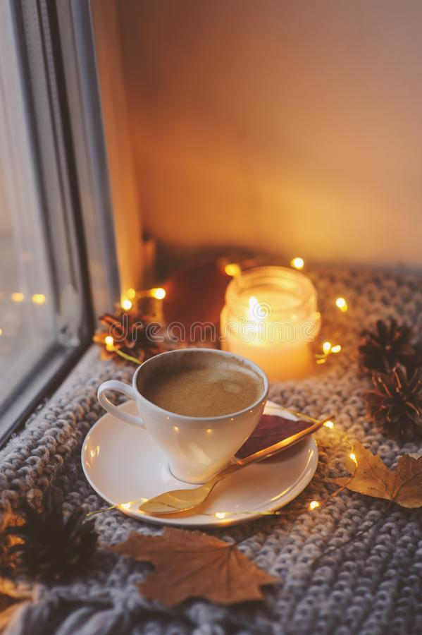 Cozy winter or autumn morning at home. Hot coffee with gold metallic spoon, warm blanket, garland and candle lights. Swedish hygge concept royalty free stock photo