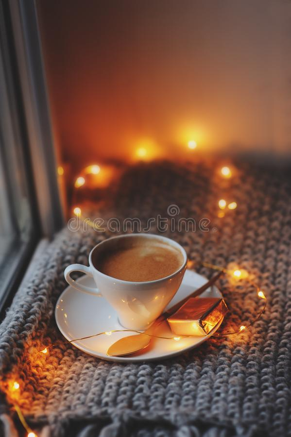 Cozy winter or autumn morning at home. Hot coffee with gold metallic spoon, warm blanket, garland and candle lights. Swedish hygge concept royalty free stock photos