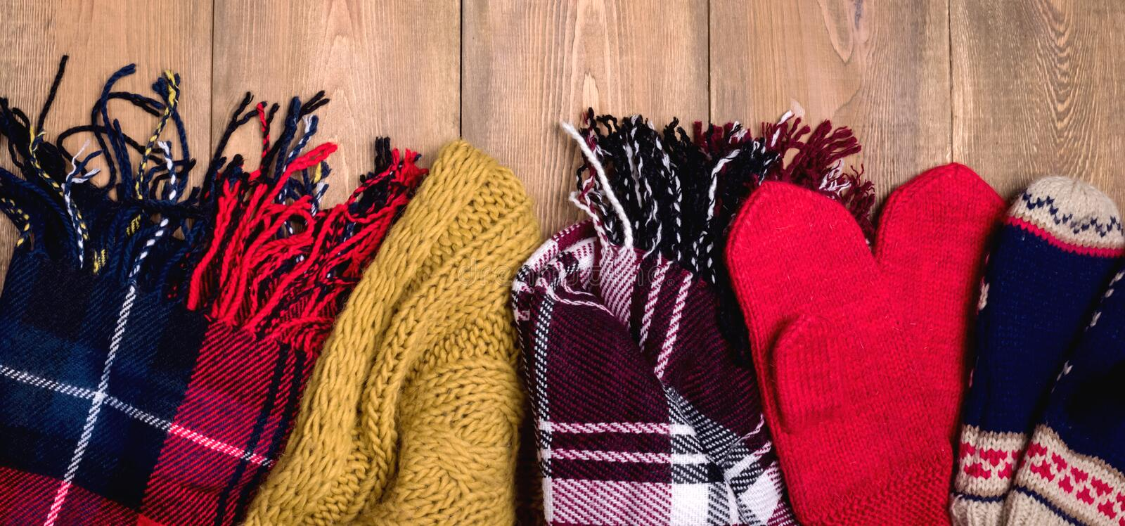 Cozy winter background Warm knitted scarfs and mittens on wooden background with space for text Top view. Copy space Long Toned stock photo