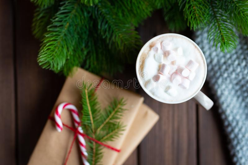 Cozy winter christmas under fir tree photo. Gifts wrapped with craft paper, decorated with candy cane and cup mug of stock photography