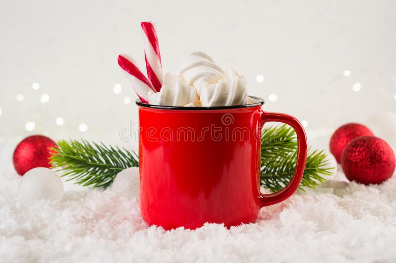 Cozy winter composition with a red cup of hot chocolate with marshmallows on a festive background stock photography