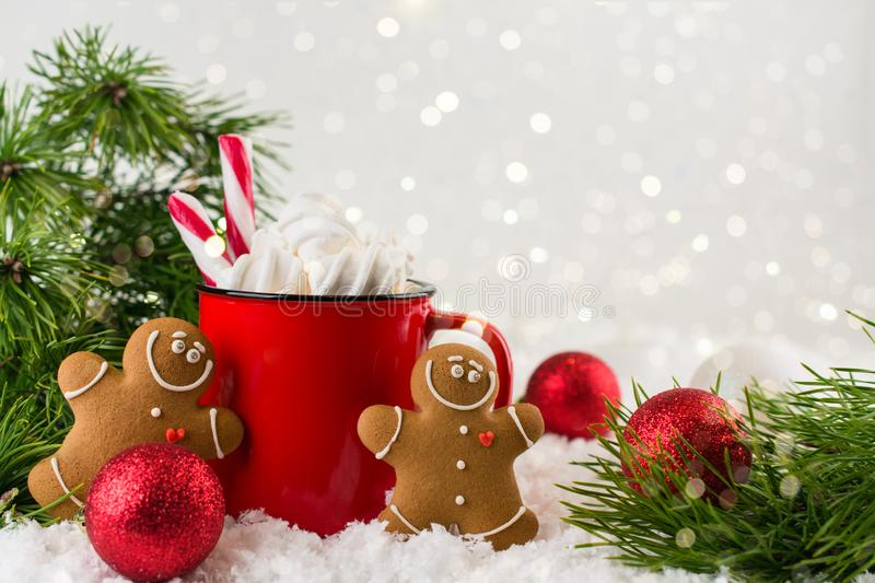 Cozy winter composition with a red cup of hot chocolate with marshmallows gingerbread man cookies on a festive background. Cozy winter composition with a red cup stock photo