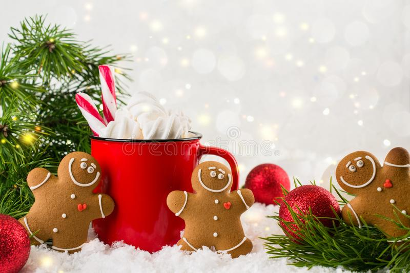 Cozy winter composition with a red cup of hot chocolate with marshmallows gingerbread man cookies on a festive background. Cozy winter composition with a red cup royalty free stock photo